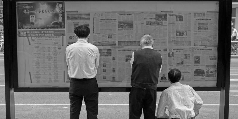 Reading newspapers on street